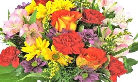 """Bright roses, daisy pompons, red carnations and purple statice arrive in clear glass vase standing 15""""H."""