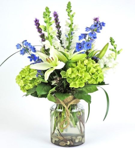 Sweet scented Casablanca lilies surrounded by green hydrangeas and additional wildflowers in a decorative modern vase with rope handle.